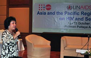speaker at left of picture holding microphone, in background is a banner saying Asia and Pacific Regional (Consultation) on HIV and