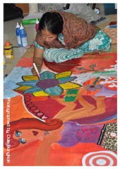 participants painting on large canvas on the floor