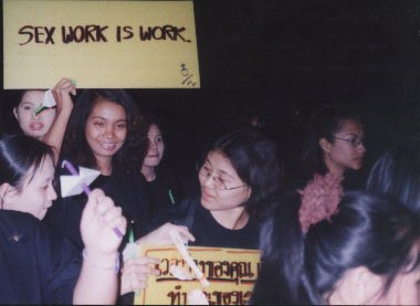 "women holding a placard saying ""Sex Work is Work"" in English, and partially visible one in Thai language"