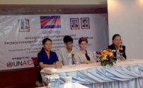 four people seated at a table in front of a banner with Cambodian flag, photos, and a UNAIDS logo visible on banner