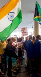Kiran holds a large Indian flag as protestors prepare to march