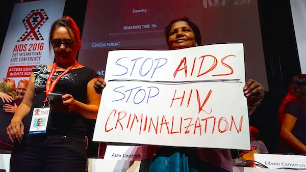 "Kiran Deshmukh holds a placard saying ""Stop AIDS Stop HIV Criminalization"""