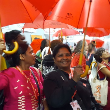 sex workers hold red umbrellas aloft as the prepre to protest at IAC 2016