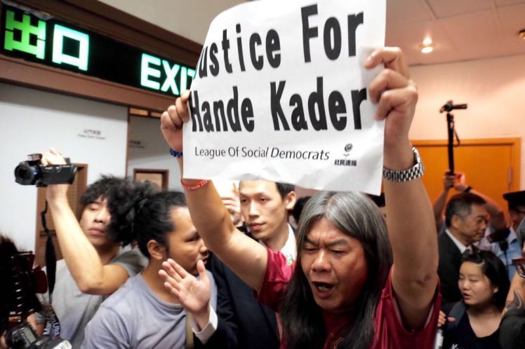 "Indoor photo of a protestor holding a sign which reads ""Justice for Hande Kader"""