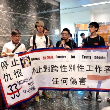 "Indoor photo of protesters holding a long banner in English and Chinese saying ""Justice for Hande Kader"" and ""There's no safe country for trans people."""