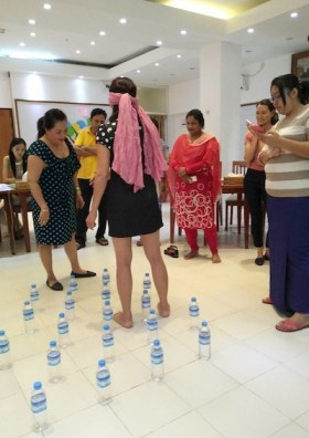 Indoor photo of a participant wearing a blindfold walking through twenty waters bottles positioned on the floor
