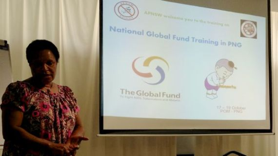 """presenter stands next to projected image saying """"National Global Fund Training in PNG"""" with APNSW and Global Fund logos"""