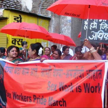 "sex workers in India march through the street carrying red umbrellas saying ""Sex work is work"" and an NNSW banner"