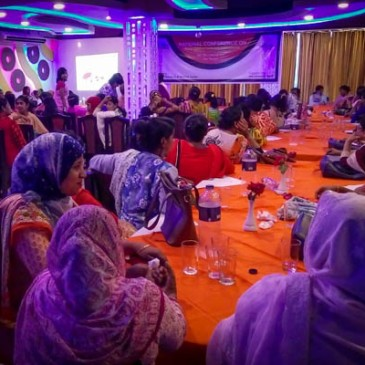 Participants at the conference sit a tables in brightly coloured venue with orange table cloths and purple lights